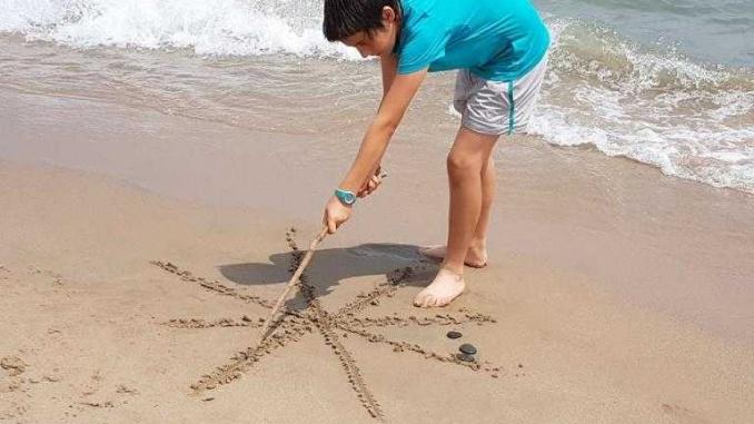 Dibuixant una estel a l'estil Miró a la platja de la Pixerota - Foto: YouMeKids