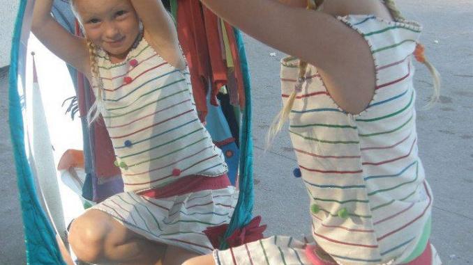 Frida, la filla de Meritxell Nogués, posant amb un dels models fets per la seva mare.